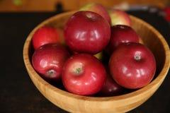 Красные яблоки в деревянном шаре на деревянном столе кабанины стоковые фото