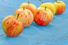 Красные яблоки на голубой деревенской предпосылке Стоковые Изображения RF