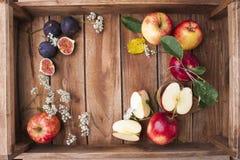 Красные яблоки на деревянной коробке с листьями и цветками Сбор осени плодоовощей Взгляд сверху Открытый космос для текста Стоковое фото RF