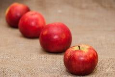 Красные яблоки на предпосылке дерюги Стоковые Фотографии RF