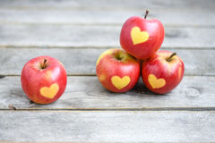 Красные яблоки с формой сердца на серой деревянной предпосылке Стоковая Фотография