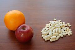 Красные Яблоко, апельсин и пилюльки на таблице Стоковые Изображения RF