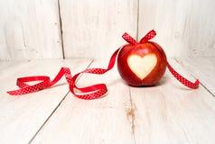 Красные яблоко и лента на деревянной предпосылке Стоковые Фотографии RF
