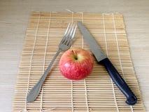 Красные яблоко и нож на крупном плане деревянного стола Стоковые Изображения