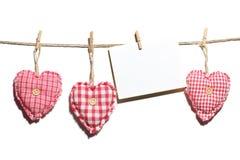 Красные handmade сердца при пустая карточка вися на линии одежд Стоковое Фото