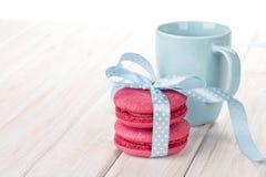 Красные macarons с чашкой голубой ленты и молока Стоковые Изображения