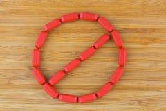 Красные multi витамины аранжируют в знаке стопа Таблетки покрытые фильмом  Стоковое Фото