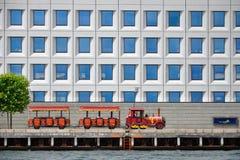 Красные sightseeing поезда едут вдоль портового района вдоль белого здания с голубыми окнами Стоковое Фото