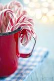 Красные striped тросточки конфеты в красной кружке Стоковые Фотографии RF