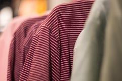 Красные striped футболки на вешалке в торговом центре стоковые изображения