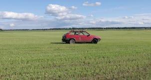 Красный автомобиль едет поле и делает фокусы сток-видео
