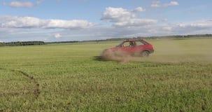 Красный автомобиль едет поле и делает фокусы видеоматериал
