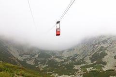 Красный автомобиль кабел-крана горы в облаках и тумане Стоковая Фотография RF