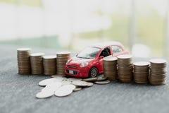 Красный автомобиль над много штабелированными монетками стоковые изображения rf
