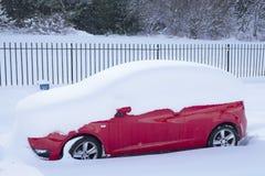 Красный автомобиль предусматриванный в глубоких снеге и крыше во время тяжелого падения на белое вещество в зиме стоковые фото