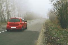 Красный автомобиль едет вдоль сельской дороги в тумане между деревьями Стоковое Фото