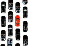Красный автомобиль игрушки стоя вне от толпы автомобиля множества идентичного черного Стоковое фото RF