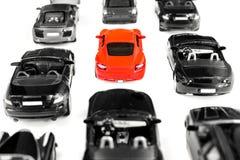 Красный автомобиль игрушки стоя вне от толпы автомобиля множества идентичного черного Стоковые Изображения RF