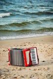 Красный аккордеон на пляже стоковые фотографии rf