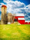 Красный амбар, голубые небеса и зеленый цвет, зеленая трава дома. Стоковые Изображения