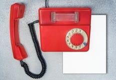 Красный античный роторный телефон с чистым листом бумаги стоковое изображение rf