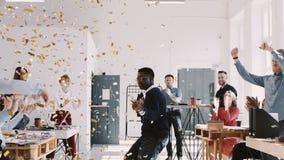 КРАСНЫЙ бизнесмен EPIC-W счастливый молодой африканский празднуя успех танцуя с confetti и командой на замедленном движении офиса акции видеоматериалы