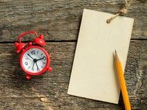 Красный блокнот будильника для записи карандаша на деревянной деревенской таблице Стоковая Фотография RF