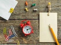 Красный блокнот будильника для записи карандаша на деревянной деревенской таблице Стоковое фото RF