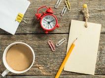 Красный блокнот будильника для записи карандаша на деревянном деревенском кофе таблицы Стоковые Фото