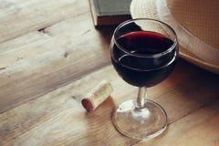 Красный бокал и старая книга на деревянном столе на годе сбора винограда взрыва захода солнца фильтровали изображение Стоковые Изображения