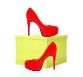 Красный ботинок женщины и желтая подарочная коробка изолированные на белизне Стоковые Изображения RF