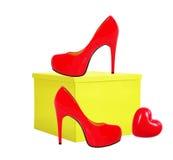 Красный ботинок женщины и желтая подарочная коробка изолированные на белизне Стоковая Фотография RF