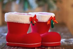 Красный ботинок рождества с белой границей и малые колоколы на деревянном столе Стоковая Фотография RF