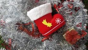 Красный ботинок santa и присутствующая коробка на серебряных декорумах рождества сусали Стоковое фото RF