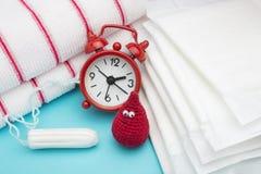 Красный будильник, мечтательное падение крови вязания крючком улыбки, ежедневные менструальные пусковая площадка и тампон и полот стоковое фото