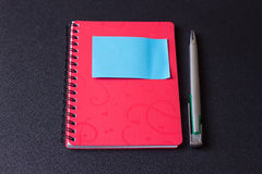Красный блокнот на спирали с стикером и ручкой стоковые изображения rf