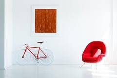 Красный велосипед под картиной в белом современном интерьере просторной квартиры с armch стоковое фото rf