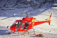 Красный вертолет приземлился на швейцарский лыжный курорт около горы Jungfrau Стоковое фото RF
