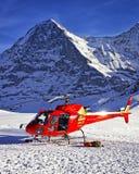 Красный вертолет приземлился около высокогорного пика около горы Jungfrau Стоковые Фотографии RF