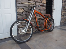 Красный велосипед стоя против стены Стоковые Изображения RF