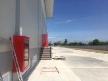 Красный гаситель шкафа пожарного рукава стеной с голубым небом стоковые фотографии rf