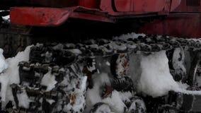 Красный гусеничный трактор извлекает снег от дороги сток-видео