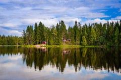 Красный деревянный коттедж озером Стоковые Изображения RF