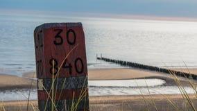 Красный деревянный поляк на море Стоковое Изображение