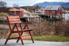 Красный деревянный стул в малой норвежской деревне Стоковая Фотография