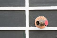 Красный жидкостный огнетушитель на стене стоковое изображение rf