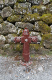 Красный жидкостный огнетушитель против каменной стены стоковые фото