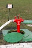 Красный жидкостный огнетушитель стоит в люке -лазе Стоковое Изображение