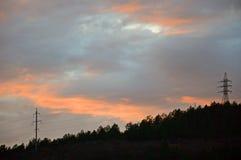 Красный заход солнца над темным ландшафтом Линия электропередач стоковые изображения rf