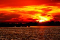Красный заход солнца с силуэтом моста Стоковые Фотографии RF